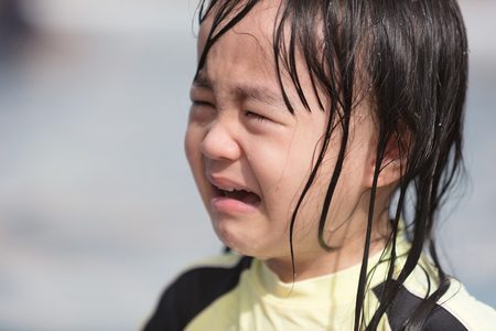 Asian Little Chinese Girl crying in Swimming Pool outdoor
