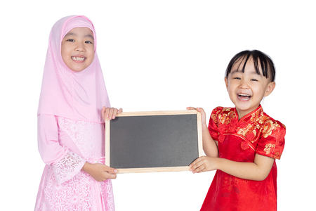 Asian Chinese little sisters wearing cheongsam and traditional Malay costume holding blackboard together in isolated white background