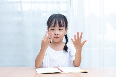 Asian little Chinese Girl doing mathematics by counting fingers at home Standard-Bild