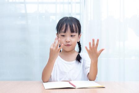 Asiatisches kleines chinesisches Mädchen, das Mathematik durch Zählen der Finger zu Hause tut