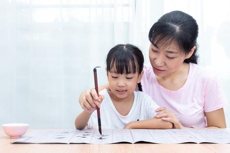 Asiatische chinesische Mutter, die Tochter unterrichtet, übt zu Hause chinesische Kalligraphie