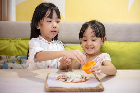 Asian Little Chinese Girls DIY mini pizza at home