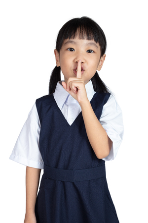 Asian Little Chinese Girl putting finger up to lips and asking for silence in isolated White Background