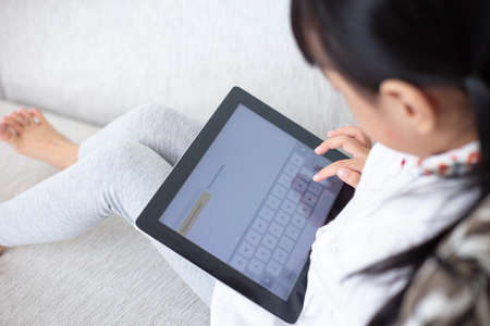 Asian Chinese little girl sitting on the sofa playing digital tablet in the living room at home