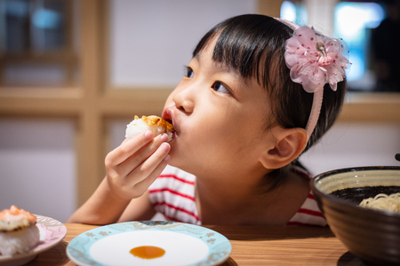 Asian little Chinese girl eating sushi at a Japanese restaurant