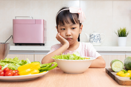 Asian Chinese little girl eating salad in the kitchen at home