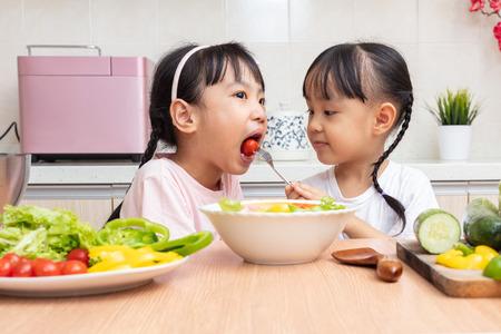Piccole sorelle cinesi asiatiche che producono insalata in cucina a casa