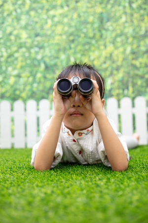 Asian Little Chinese girl kneeling on the grass and playing with telescope at outdoor park