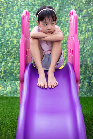 Asian Chinese Little Girl Playing on the slide at outdoor playground