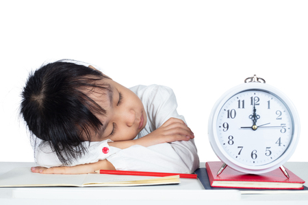 Asian Chinese Little Girl sleeping on desk when doing homework in isolated white background Banque d'images