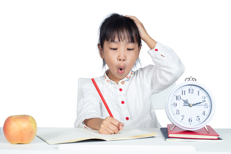 Asian Chinese Little Girl doing homework in isolated white background Фото со стока