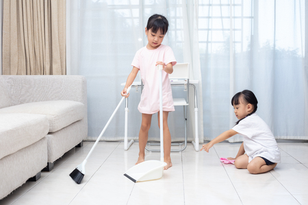 Asian Chinese little sisters helping doing cleaning at home Banco de Imagens