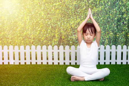 Asian Chinese little girl practicing yoga pose on a mat outdoor