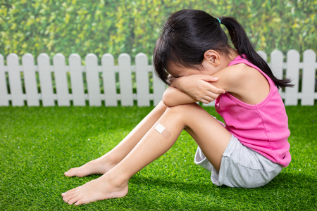 Asian Little Chinese girl sitting on the grass and crying at outdoor park