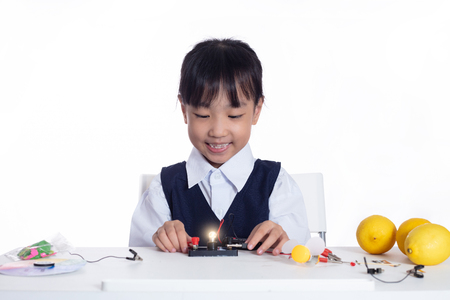 Asian chinese little girl doing experiments in isolated white background