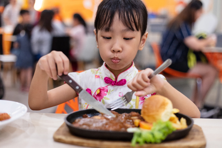 Asian Chinese little girl eating Western Food in restaurant