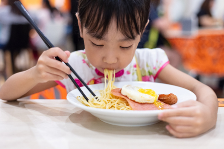Asian Chinese little girl eating noodles with chopsticks in restaurant