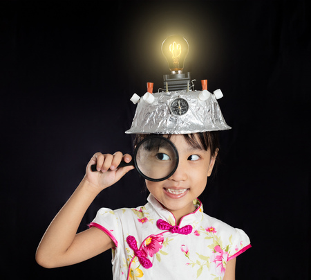 Asian chinese little girl holding magnifier with virtual reality helmet in isolated black background Stock Photo
