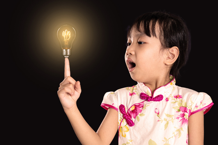 Asian chinese little girl pointing finger up to light bulb in isolated black background
