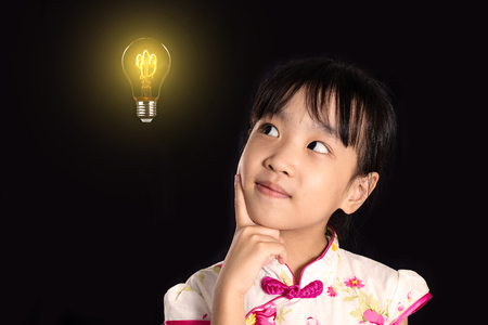 Asian Chinese little girl thinking with light bulb in isolated black background