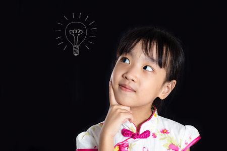 Asian Chinese little girl thinking with bulb sketch in isolated black background