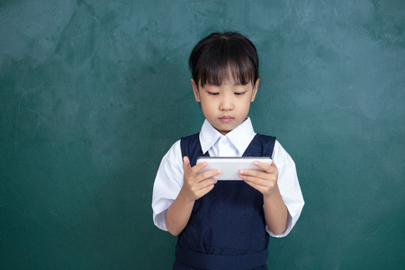 Asian Chinese little Girl in uniform playing digital tablet against green blackboard in classroom 写真素材