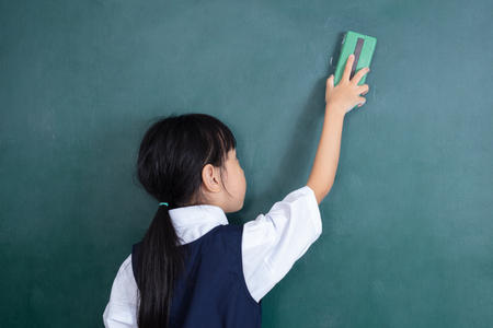 Asian Chinese little girl wiping the green blackboard in the classroom