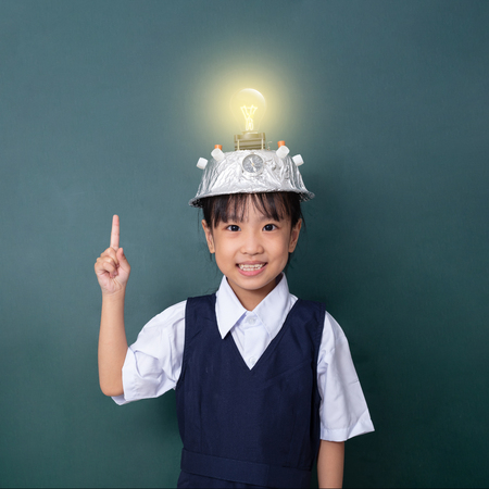 Asian chinese little girl wearing virtual reality helmet and pointing finger up to light bulb against green blackboard