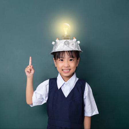 Asiatisches chinesisches kleines Mädchen, das Virtual-Reality-Helm trägt und mit dem Finger auf die Glühbirne gegen die grüne Tafel zeigt? Standard-Bild