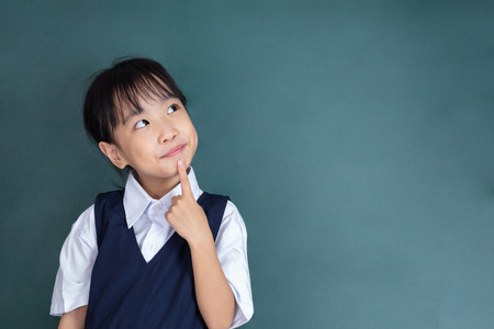 Asian Chinese little Girl thinking with finger on chin against green blackboard