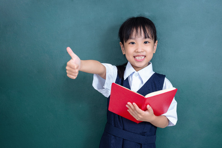Asian Chinese little Girl in uniform showing thumbs up against green blackboard in classroom