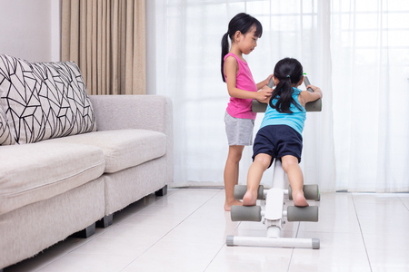 Asian Chinese little sisters playing workout machine in the living room at home