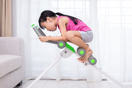 Asian Chinese little Girl playing workout machine in the living room at home