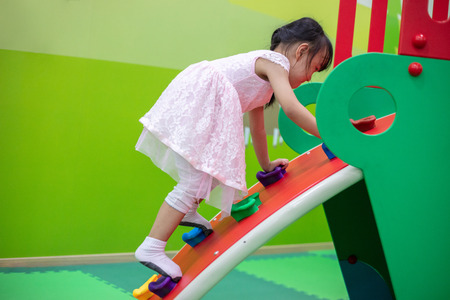 Asian Chinese little Girl playing at mini rock climbing wall at Indoor Playground