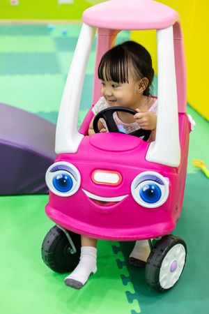 Asian Chinese little girl driving toy car at indoor playground