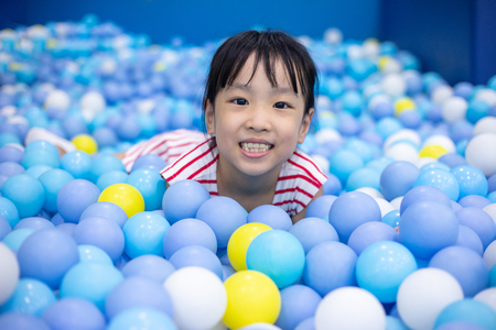 Asian Chinese little Girl Playing At Balls Pool in Indoor Playground