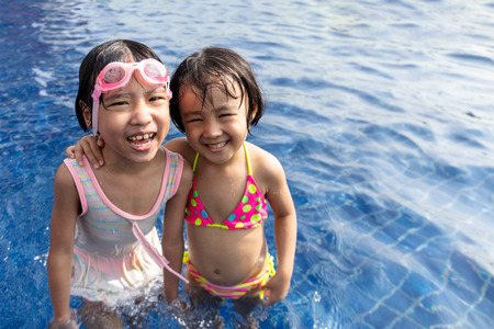 Asian Little Chinese Sisters Playing in Swimming Pool Outdoor