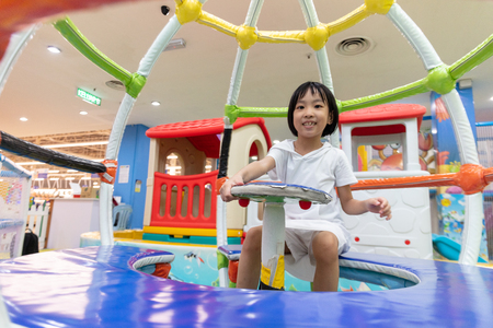 Asian Chinese little girl sitting in the carousel at indoor playground 스톡 콘텐츠