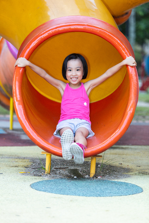 Asian Chinese little girl playing at outdoor playground alone