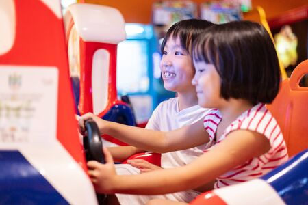 Asian Little Chinese Sisters playing at amusement indoor