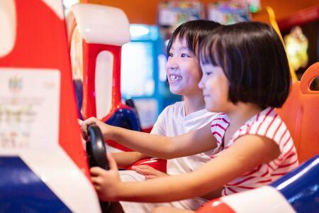 Hermanitas chinas asiáticas jugando en el interior de la diversión