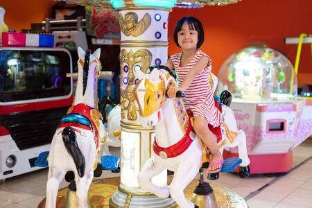 Asian Little Chinese Girl playing at amusement indoor 스톡 콘텐츠