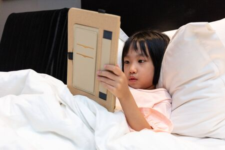 Asian Little Chinese Girl playing with tablet on bed at home