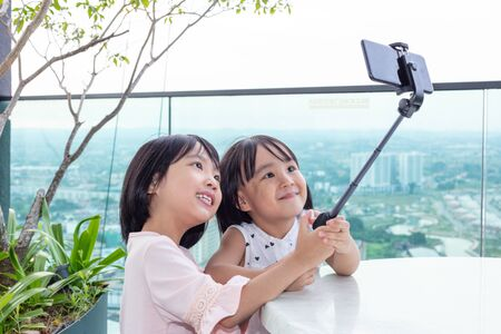 Asian Little Chinese Sisters taking selfie with smartphone on selfie stick in the outdoor cafe
