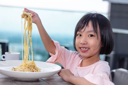 Asian Little Chinese Girl eating spaghetti in the outdoor cafe 스톡 콘텐츠