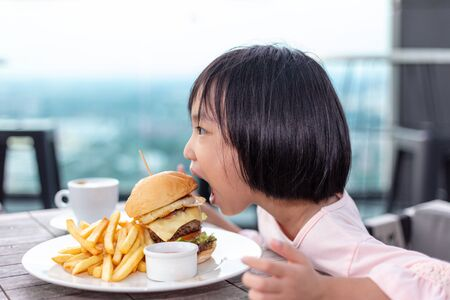 Asian Little Chinese Girl eating hamburger in the outdoor cafe 스톡 콘텐츠