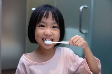 Asian Little Chinese Girl brushing her teeth in the restroom