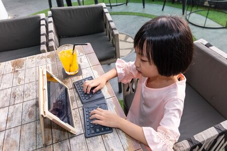 Asian Little Chinese Girl playing with tablet in the outdoor cafe 스톡 콘텐츠