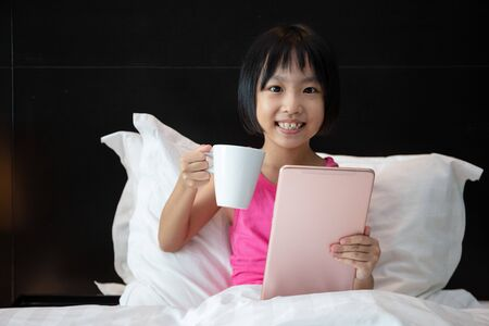 Asian Little Chinese Girl playing tablet in bed at home