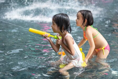 Asian Little Chinese Sisters playing at water park outdoor